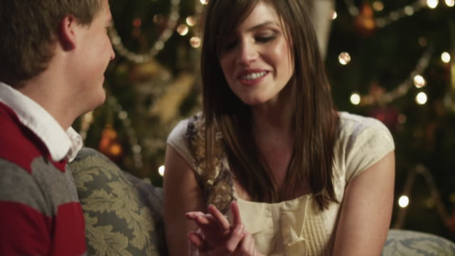 MS TD TU Young man putting engagement ring on girlfriend's finger, sitting by Christmas tree / Cedar Hills,Utah,USA