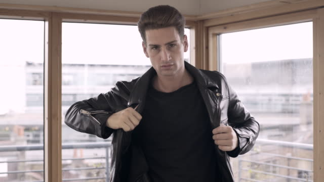 A young man putting his leather jacket on.