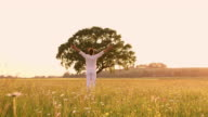 WS Young man raising his arms to the sky while standing in a meadow