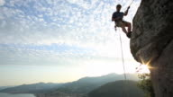 Young man rappels (abseils) as sun rises behind
