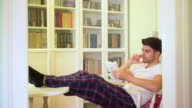 Young man reading a book in the home library