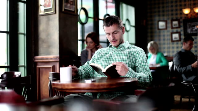 Young man reading book at a cafe