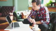 Ung man läsa på laptop på kafé.