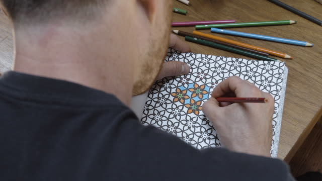 Young man relaxing by drawing in an adult coloring book - model released.