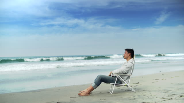WS Young man relaxing in a beach chair by the ocean