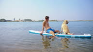 Young man relaxing on the paddleboard with his dog