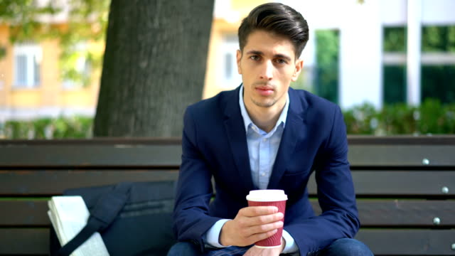Young man relaxing with coffee on the park bench