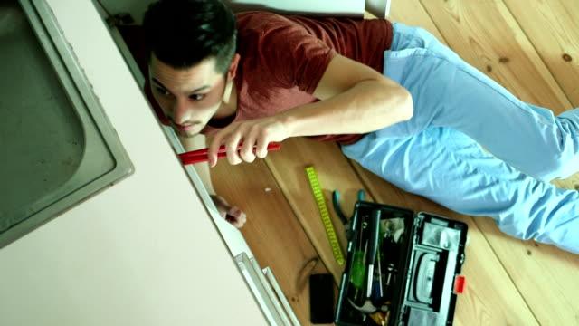 Young man repairing sink