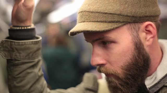A young man rides the subway.