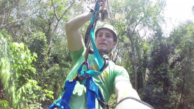 POV young man rides zipline in Belize