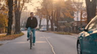 SLO MO Young man riding a bicycle along treelined road