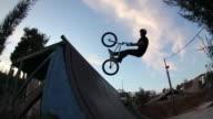 A young man riding a BMX bicycle.