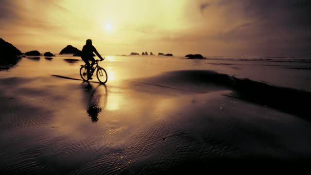 Young man riding mountain bike on Pacific beach at sunset