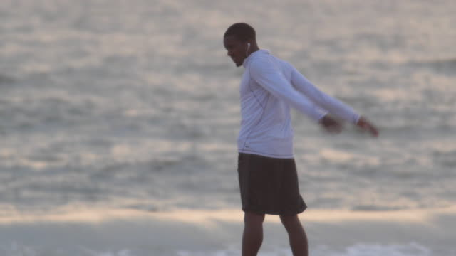 A young man runner  stretching on the beach at sunset.