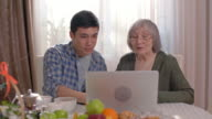 Young man showing old woman how to use laptop