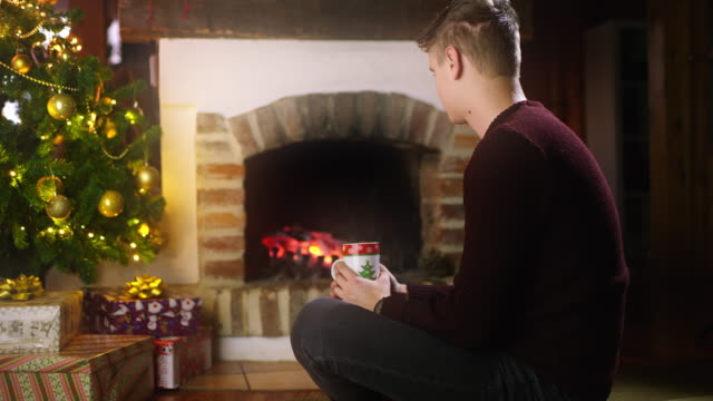 DS Young man sitting alone by the fireplace