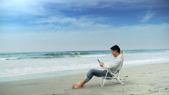 WS Young man sitting in a beach chair by the ocean