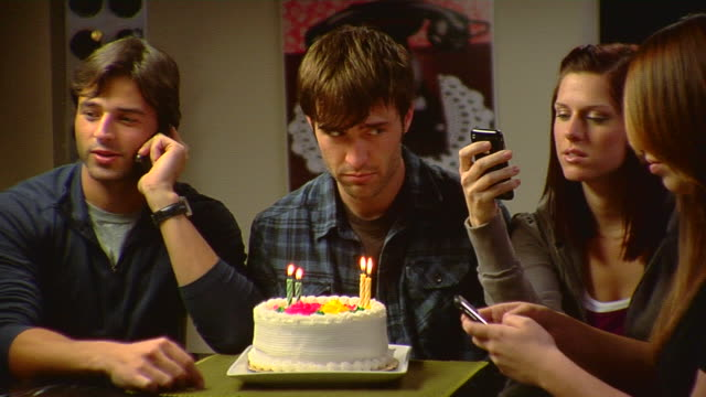 MS Young man sitting in front of birthday cake while people around him using mobile phones, Los Angeles, California, USA