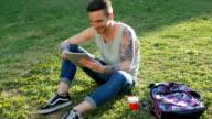 Jonge man zitten in park met digitale tablet en het gebruik van wi-fi internet