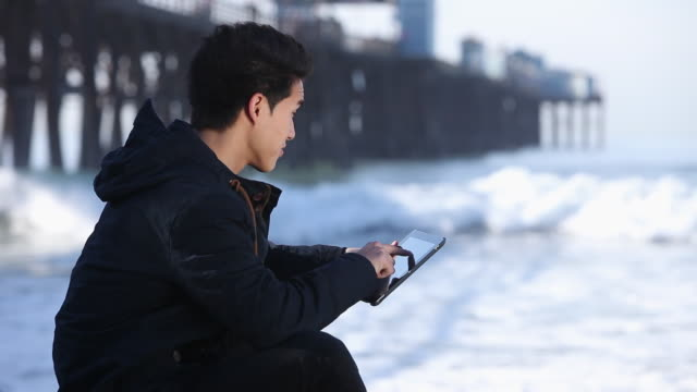 MS Young man sitting next to pier with digital tablet device