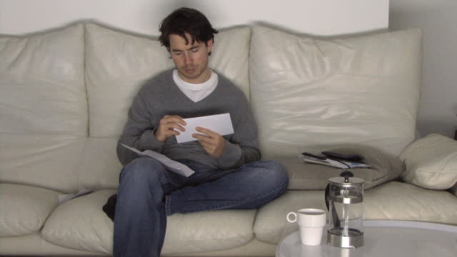 MS Young man sitting on sofa sorting finances / Hackney, United Kingdom