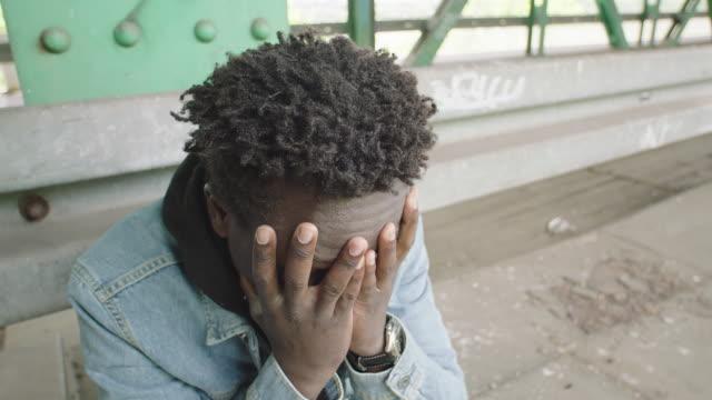 Young man sitting under bridge. Loneliness