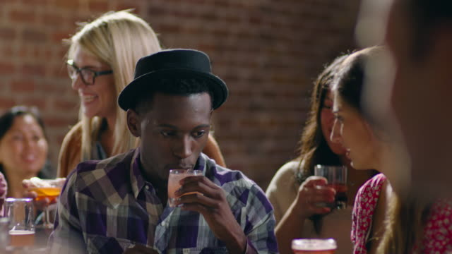 Young man smells and tastes specialty cocktail in crowded bar