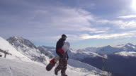 A young man snowboarder walking with his board on a scenic snow covered mountain top. - Slow Motion