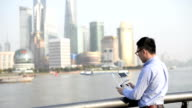 Young man standing on the Bund using a remote control to drive the drone, Shanghai, China