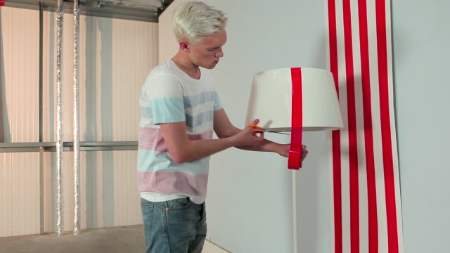 Young man sticking red tape to lampshade
