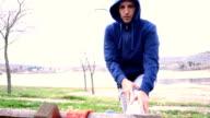 Junger Mann Dehnung auf einer Bank im Park