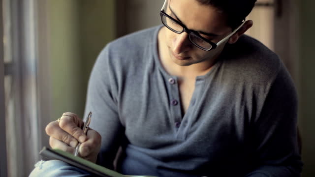 Young man studying, writing at home and thinking.