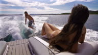 Young man surfing behind a boat, woman sunbathing