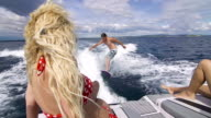 Young man surfing behind boat, girl sunbathing on boat