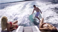 Young man surfing behind boat, two girls sunbathing on boat