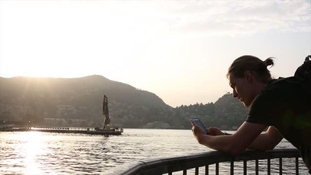Young man takes pic across lake at sunset, towards town center