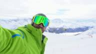 Young man takes selfie portrait on ski slopes
