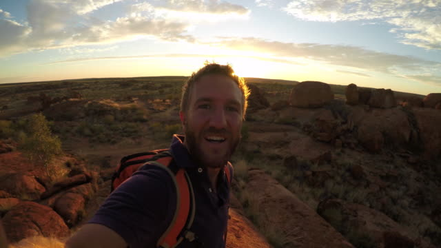 Young man takes selfie portrait with spectacular landscape at sunrise-4K
