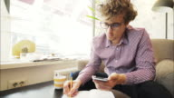 Young man taking notes while using a smart phone.