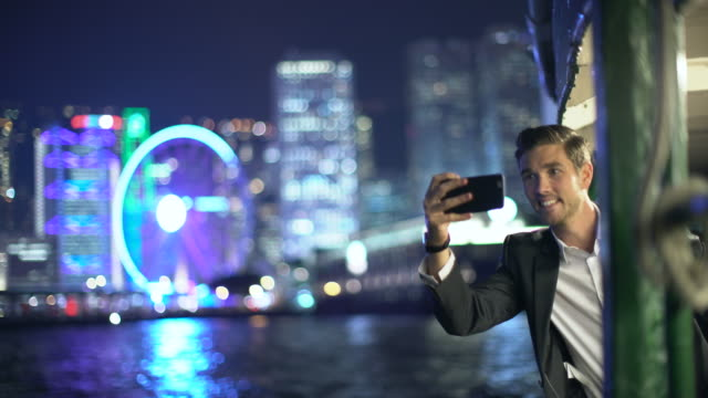 WS TS young man taking photos on a ferry at night, Hong Kong