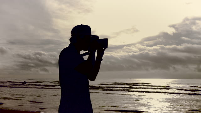 Junger Mann mit einer Kamera am Strand fotografieren