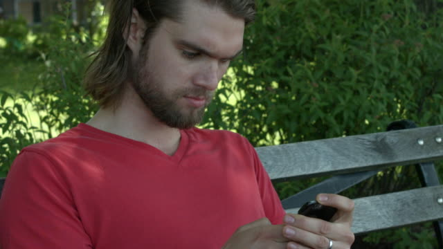 A young man texting and searching his cell phone on a bench outside in New York City
