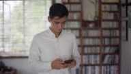 MS young man texting on a smartphone in front of a bookcase