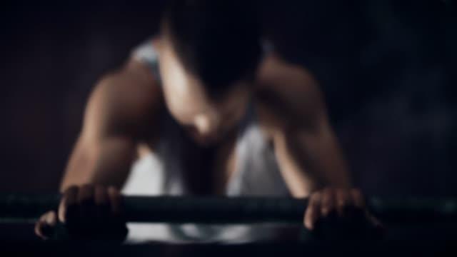 Junger Mann Training auf Klimmzugstange in Turnhalle