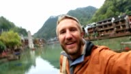 Young man traveling in China takes selfie portrait