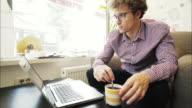 Young man typing at laptop.