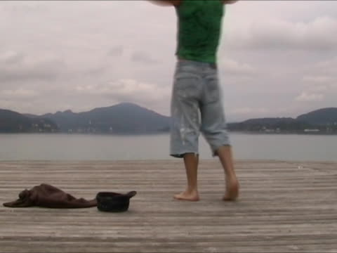 Young man undresses and jumps into the water