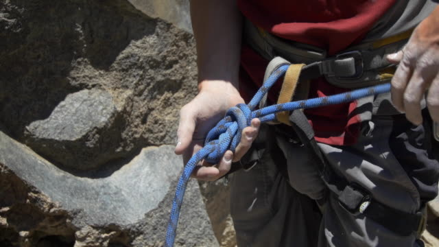 A young man using a figure eight follow-through knot to tie his rope to his harness while rock climbing.