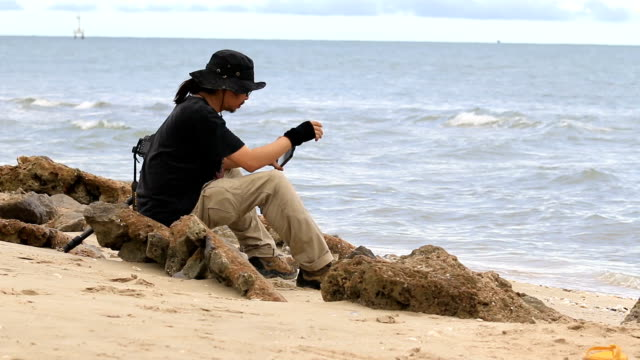 Young man using a tablet pc outdoors on the beach