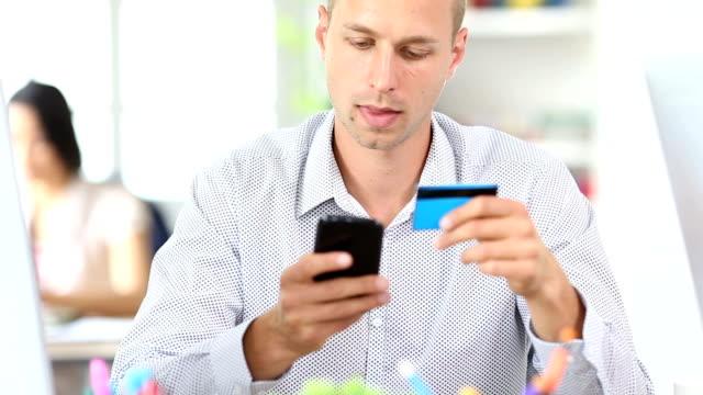 HD-Jüngling mit Kreditkarte für kontaktloses Bezahlen in Arbeitsplatz
